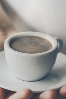 Gros plan d'un espresso café savoureux avec de la mousse savoureuse dans une petite coupe en céramique. main mâle tenant une boisson chaude chaude.