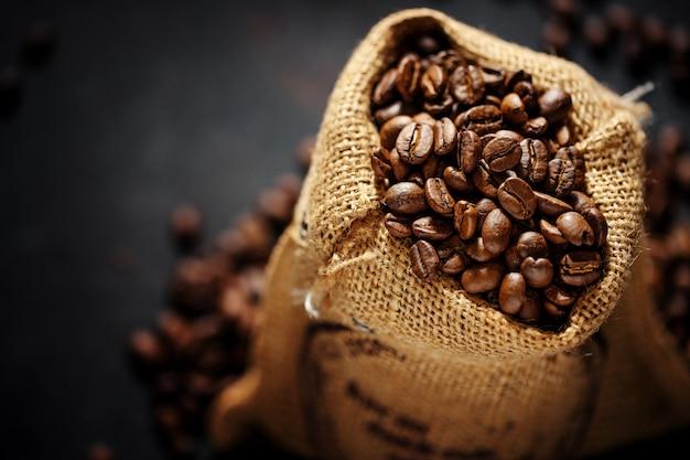 Gros plan sur l'espresso en grains de café dans un sac en jute.