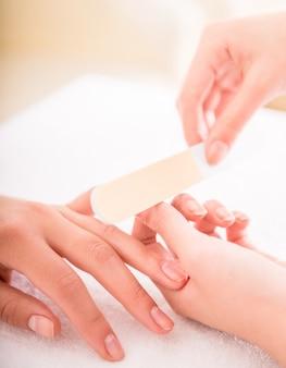 Gros plan d'une esthéticienne en train de polir les ongles d'une cliente.