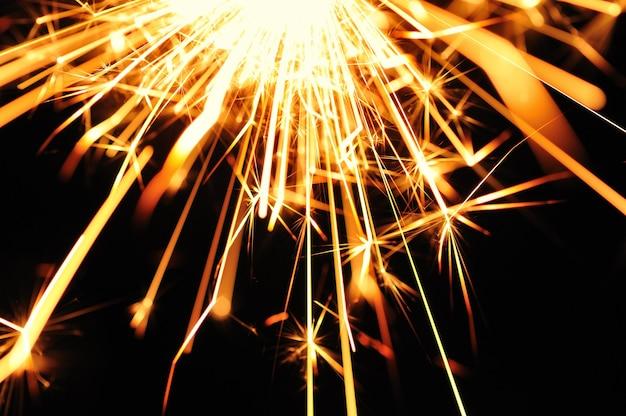 Gros plan d'étincelles floues dorées brûlent dans l'obscurité à la lumière des bougies festives