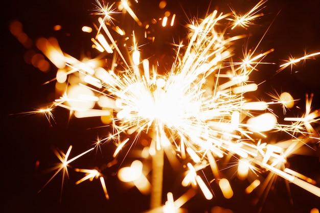 Gros plan d'étincelles floues dorées brûler dans l'obscurité à la lumière des bougies festives
