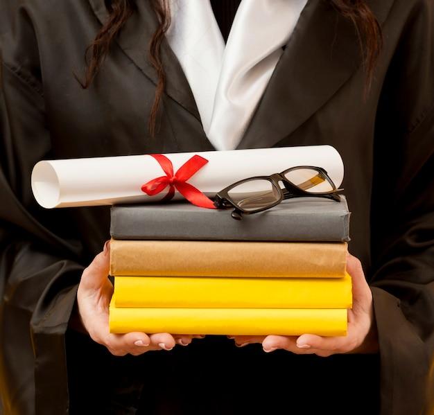 Gros plan, étudiant diplômé, tenue, livres