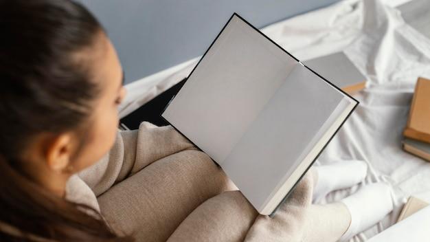 Gros plan, étudiant, lecture, dans lit