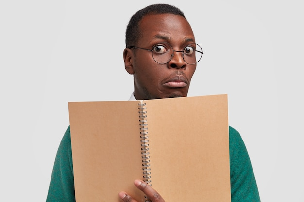 Gros plan d'un étudiant noir stupéfait vient en conférence, tient un cahier à spirale pour écrire des informations, porte des lunettes optiques