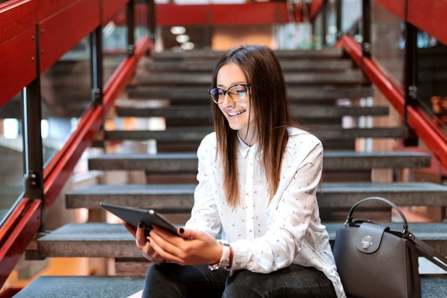 Gros plan d'une étudiante souriante avec des lunettes et des cheveux bruns à l'aide d'une tablette tout en étant assis sur les escaliers.