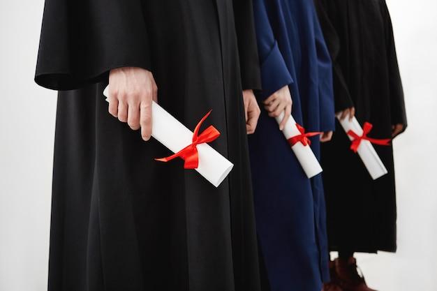 Gros plan des étudiants universitaires diplômés en manteaux titulaires de diplômes.