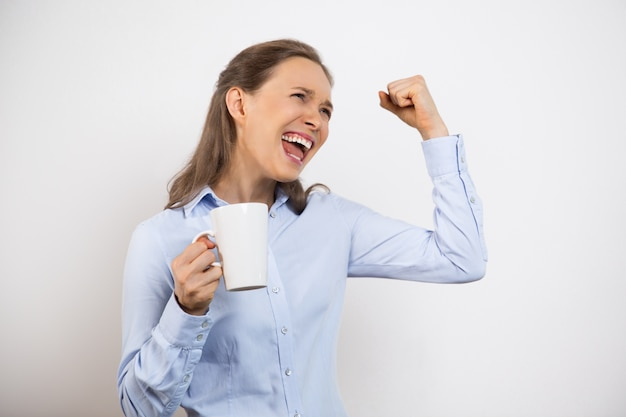 Gros plan d'euphorique enthousiaste femme tasse tenir