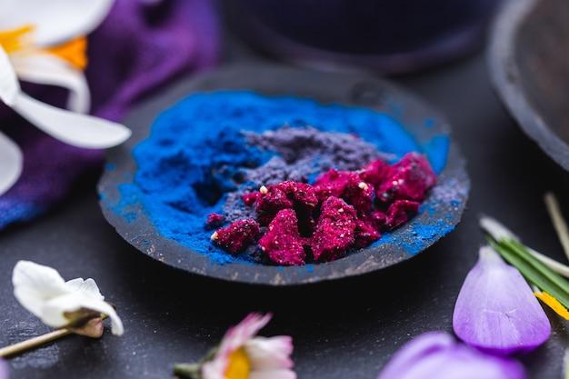 Gros plan extrême de poudre violette et bleue sur une coquille de noix de coco
