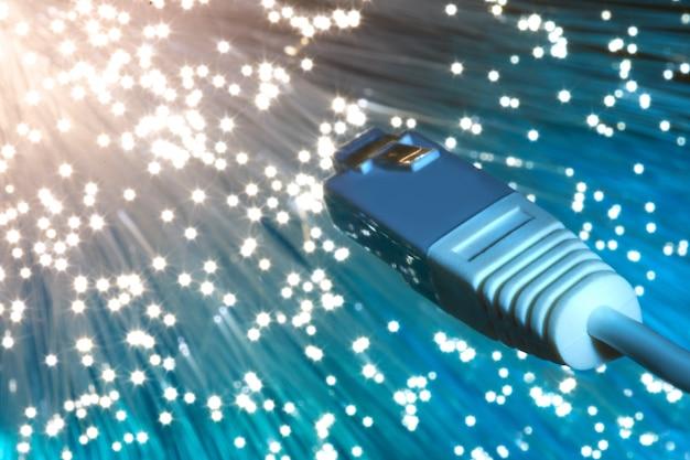 Gros plan sur l'extrémité du câble de réseau de fibre optique sur bleu