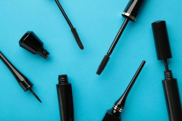 Gros plan sur des eye-liners noirs et une brosse à mascara sur fond bleu. vue de dessus.
