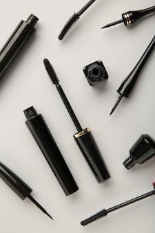 Gros plan sur des eye-liners noirs et une brosse à mascara sur fond gris. photo verticale.