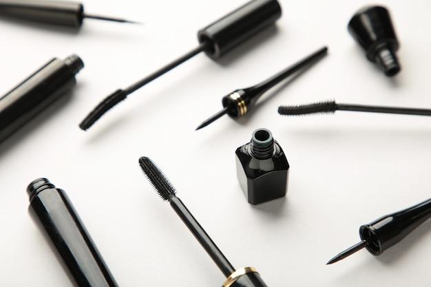 Gros plan sur des eye-liners noirs et une brosse à mascara sur fond gris. vue de dessus.