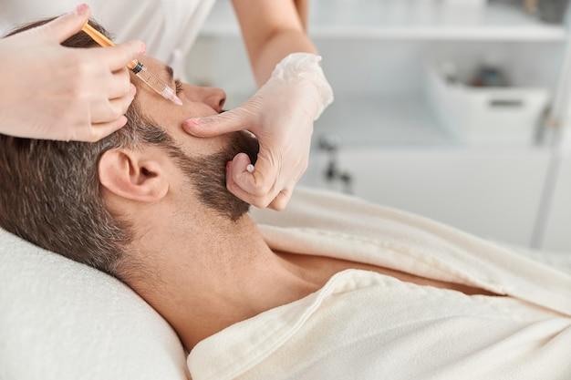 Gros plan fait des injections de mésothérapie au jeune homme. traitement du mâle par une esthéticienne pour raffermir et lisser les rides de la peau du visage.