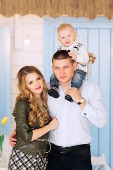 Un gros plan d'une famille heureuse, père tenant un fils sur son cou et étreignant sa femme