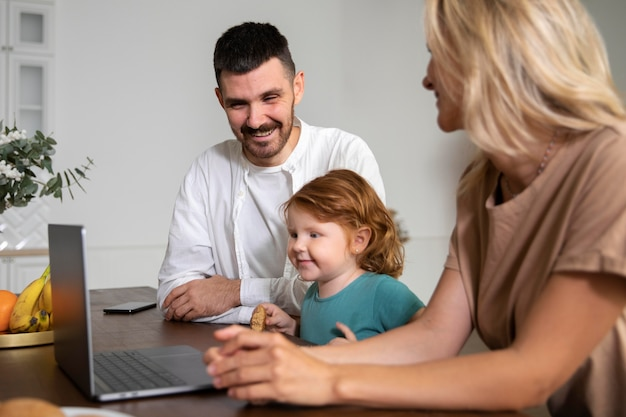 Gros plan sur la famille à la maison avec un ordinateur portable