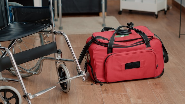 Gros plan sur un fauteuil roulant et un sac de soins infirmiers sur le sol de la maison de soins infirmiers