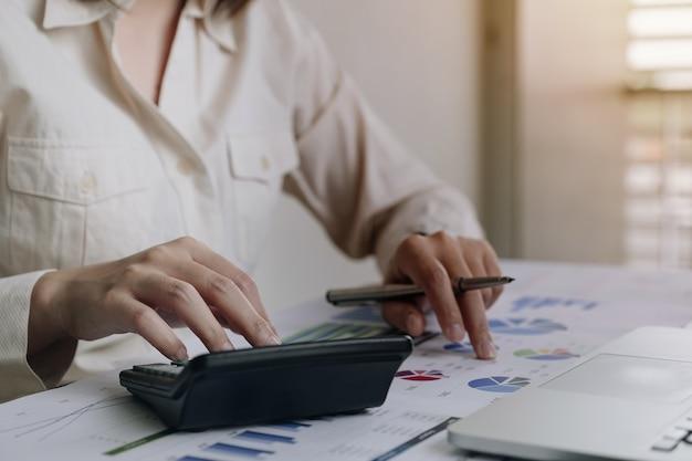 Gros plan femme d'affaires à l'aide de la calculatrice et d'un ordinateur portable pour faire des finances mathématiques sur un bureau en bois