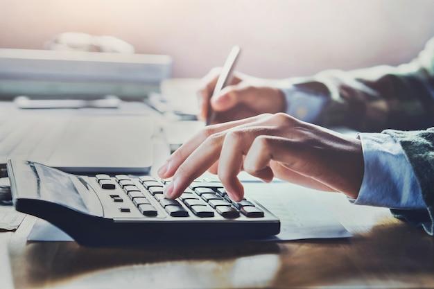 Gros plan femme d'affaires à l'aide de la calculatrice pour calculer les finances et la comptabilité
