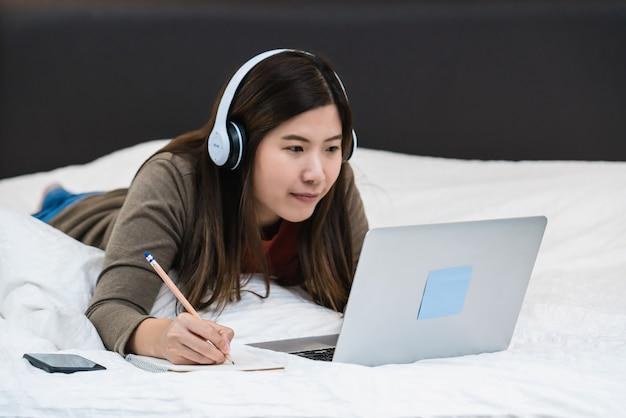 Gros plan d'une femme d'affaires asiatique écrivant à la main et utilisant un ordinateur portable technologique pour le travail à domicile