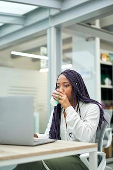 Gros plan de femme d'affaires assis au bureau de boire du café tout en travaillant sur un ordinateur portable