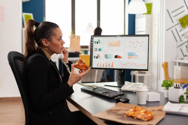 Gros plan d'une femme d'affaires assise au bureau devant un ordinateur en train de manger une tranche de pizza