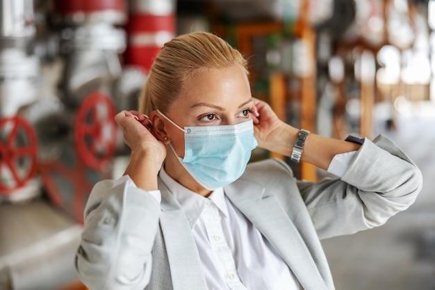 Gros plan d'une femme d'affaires blonde en costume mettant un masque tout en se tenant dans son usine pendant le virus corona.