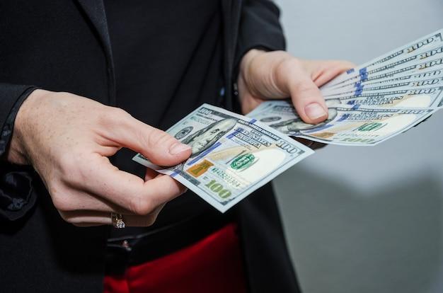 Gros plan d'une femme d'affaires compte les dollars concept financier