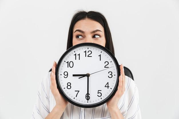 Gros plan d'une femme d'affaires excitée montrant un réveil isolé sur un mur blanc