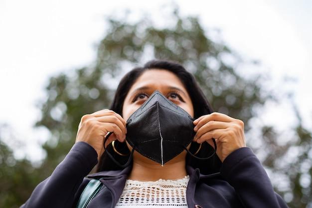Gros plan de la femme d'affaires latine portant un masque facial pour des raisons de protection pendant la pandémie de covid