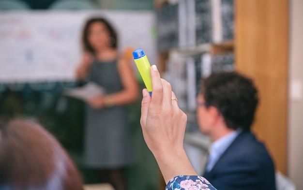 Gros plan sur une femme d'affaires levant la main avec un surligneur pour poser des questions lors d'une réunion d'affaires
