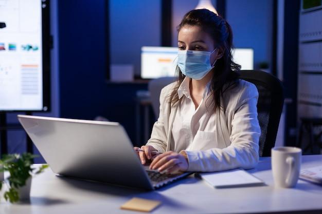 Gros plan d'une femme d'affaires avec un masque facial vérifiant les e-mails