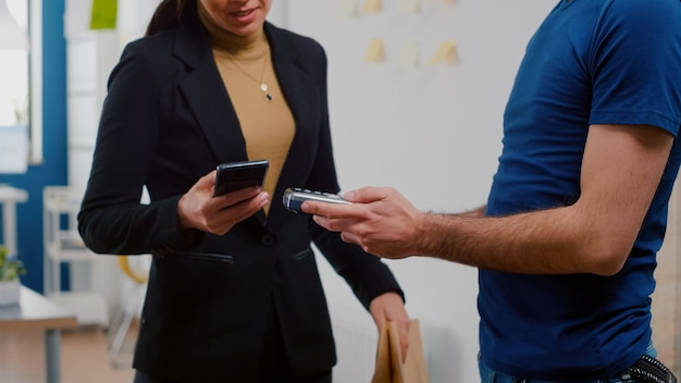 Gros plan d'une femme d'affaires payant une commande de déjeuner à emporter avec un smartphone à l'aide de pos