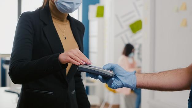 Gros plan d'une femme d'affaires payant une commande de plats à emporter avec une carte de crédit à l'aide du service sans contact pos