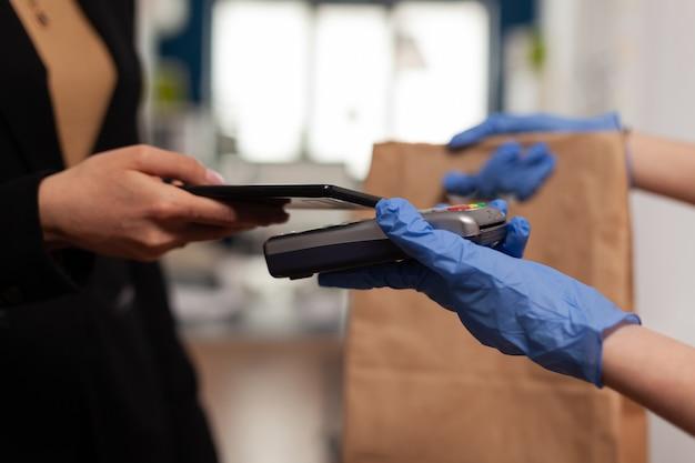 Gros plan d'une femme d'affaires payant une commande de repas à emporter avec un smartphone à l'aide du service sans contact pos pendant l'heure du déjeuner à emporter sur le lieu de travail de l'entreprise. livreur apportant un repas frais.