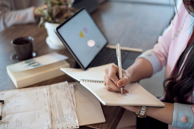 Gros plan, de, femme affaires, prendre notes, dans, ordinateur portable, bureau, bureau