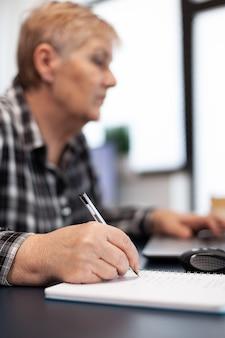Gros plan d'une femme d'affaires senior écrivant des notes sur un ordinateur portable femme âgée dans le salon de la maison à l'aide de ...