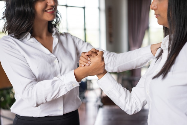 Gros plan d'une femme d'affaires souriant soutenant un collègue au café.