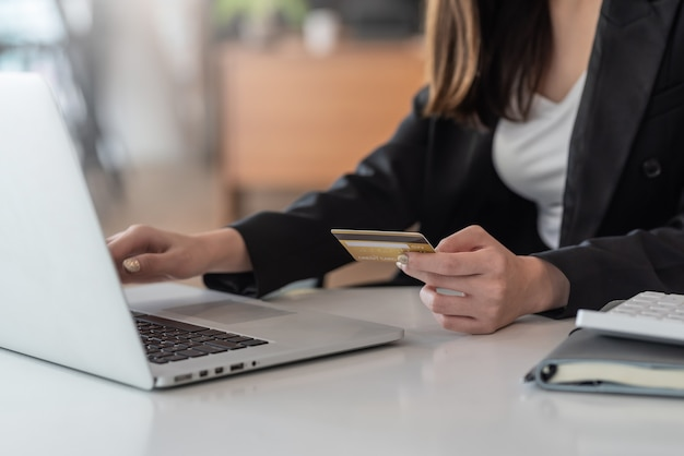 Gros plan d'une femme d'affaires tenant une carte de crédit en ligne à l'aide d'un ordinateur portable au bureau.