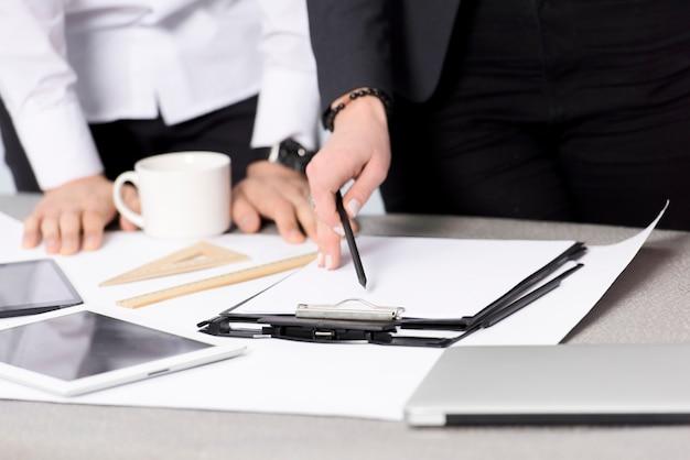 Gros plan, femme affaires, tenue, crayon, papier, presse-papiers, bureau