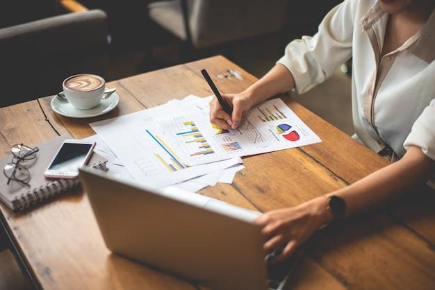 Gros plan de femme d'affaires travaillant avec des documents et un ordinateur portable au bureau. concept d'entreprise