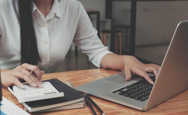 Gros plan femme d'affaires utilisant une calculatrice et un ordinateur portable pour calculer la finance, la fiscalité, la comptabilité, les statistiques et le concept de recherche analytique
