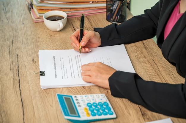 Gros plan sur une femme d'affaires utilisant les finances du ménage de la machine de calcul ou les taxes sur la machine, les concepts de finance et de comptabilité,