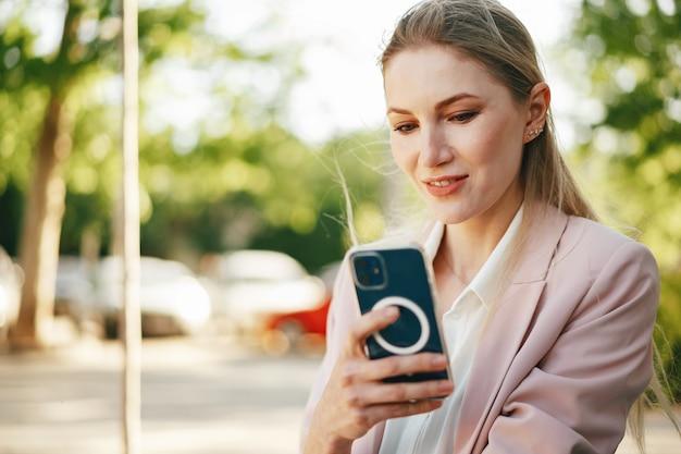 Gros plan d'une femme d'affaires utilisant un smartphone à l'extérieur de la ville