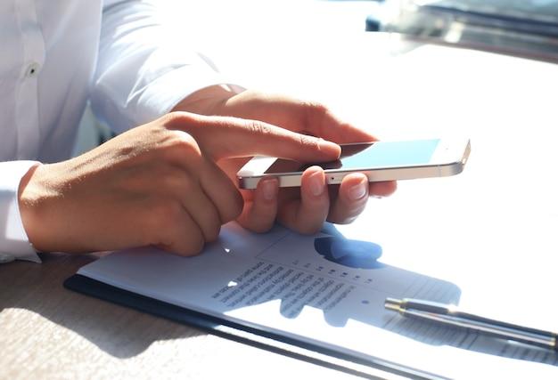 Gros plan d'une femme d'affaires utilisant un téléphone intelligent mobile