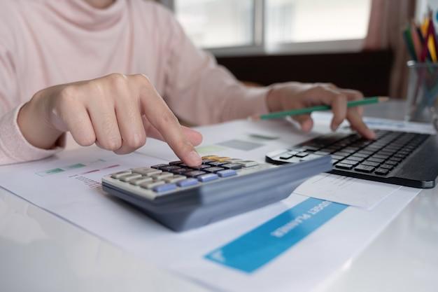 Gros plan, femme affaires, utilisation, calculatrice, et, ordinateur portable, faire, math, finances, bureau, bois, bureau