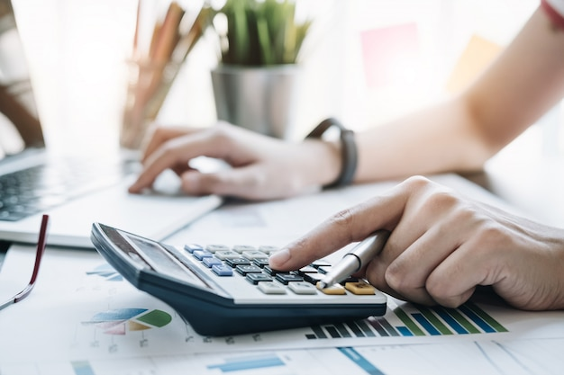 Gros plan, femme affaires, utilisation, calculatrice, et, ordinateur portable, finance, maths, bureau, bois, bureau