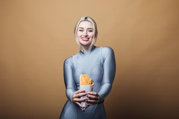 Gros plan d'une femme affamée avec sourire, tenant et mangeant un gros sandwich. concept de restauration rapide