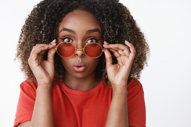 Gros plan d'une femme afro-américaine féminine séduisante surprise et amusée aux cheveux bouclés enlevant des lunettes de soleil et pliant les lèvres d'étonnement et d'intérêt réagissant à une scène impressionnante