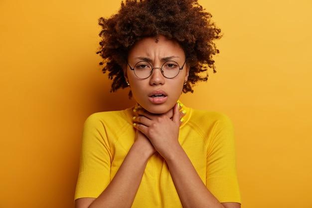 Gros plan d'une femme afro-américaine frisée frustrée garde les mains sur le cou