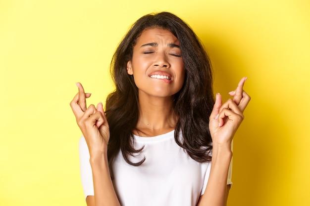 Gros plan d'une femme afro-américaine inquiète suppliant de se mordre la lèvre et de fermer les yeux tout en faisant un vœu...